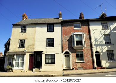 Old English houses with chimney in the corner under blue sky and sunny day, England, UK