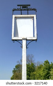 An old English pub sign against a blue sky, blank for your own image.