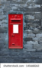 Old English red post box set in a wall