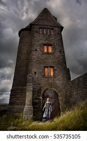 Old English stone tower building with medieval woman standing in period dress before it