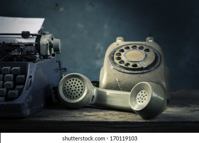 Old English type writer with paper sheet and telephone, still life