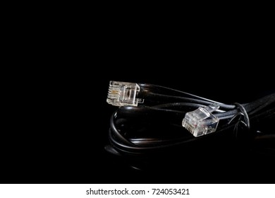 Old entangled cables, electronics and old cable connectors on a black table. Black background