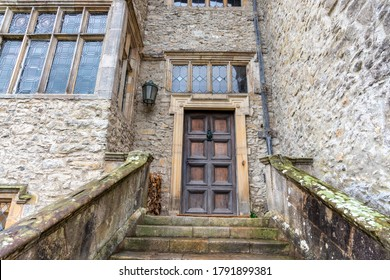 Old entrance wooden door with stone steps and mullioned windows.