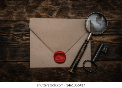 Old envelope with a sealing wax stamp, rusty key and a magnifying glass on a brown wooden table background with a copy space.
