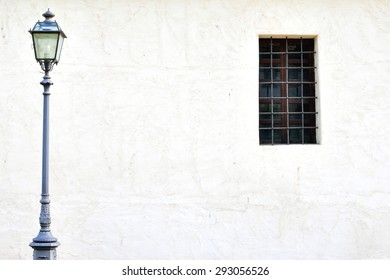 Old european house background: lantern and window at the dirty white wall