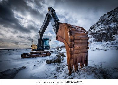 Old excavator with excavator bucket in winter. Road construction in snow. Lofoten islands, Norway. High dynamic range HDR image