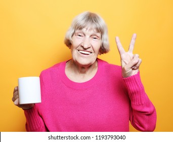 old excited lady smiling laughing, holding cup drinking coffee, tea, beverage on yellow background
