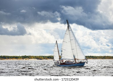 Old expensive vintage wooden sailboat (yawl) close-up, sailing under dramatic sky before the thunderstorm. Sailing yacht regatta. Epic cloudscape. Kiel, North Germany