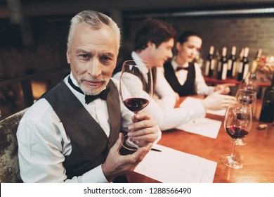 Old experienced sommelier in bow tie is holding glass of red wine while sitting at table. Confident sommelier checks aging of wine