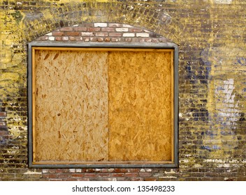 A old exterior brick wall with an old boarded up window ready for your content