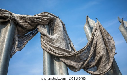 Old fabric cloth caught on metal spiked security barrier.