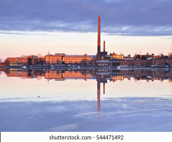 Old factory buildings by frozen sea. Reflection on ice and water. Architectural landscape.