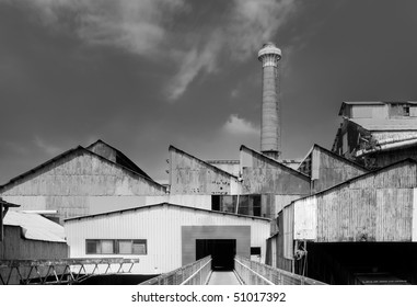 Old factory exterior with buildings and chimney.
