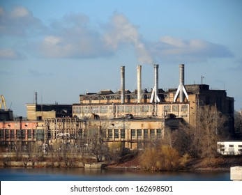 The old factory with smoking chimneys on the banks of the river