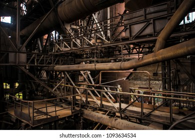 Old factory with sun beams. Horizontal industrial retro photography.Old factory horizontal photography. Metal planks and pipes. Dark industrial interior of large  hall for manufacturing or warehousing