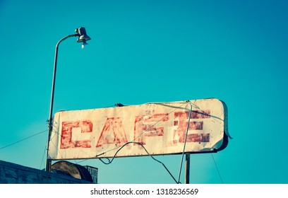 Old faded cafe sign on an abandonned building in the salton sea, California,vintage cross processed effect