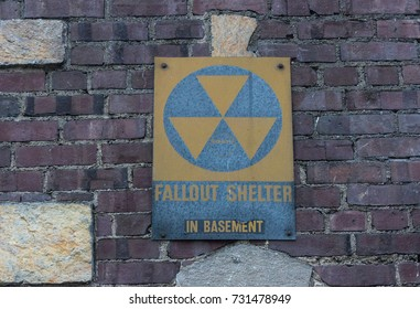 Old faded Fallout Shelter Sign on grungy Brick Wall background