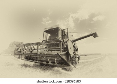 Old faded image of combine harvester parked in wheat field on summer day