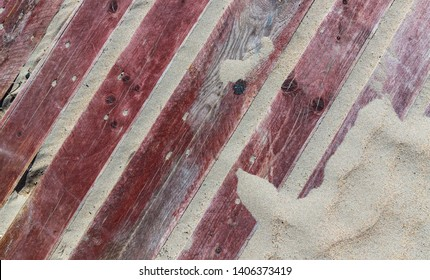 old faded red wooden pallet in the sand, grungy  background texture