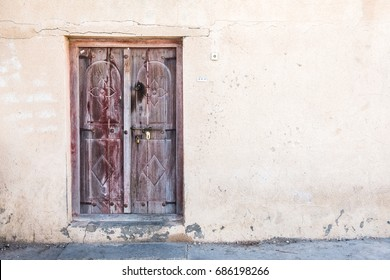 An old faded traditional Arabian carved wooden door in the cracked weathered wall of a simple house.