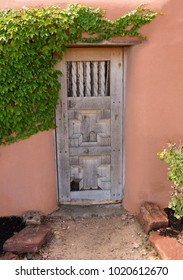 Old faded wooden door set within walls of Adobe earthen wall structure with green ivy growing across the fascade.