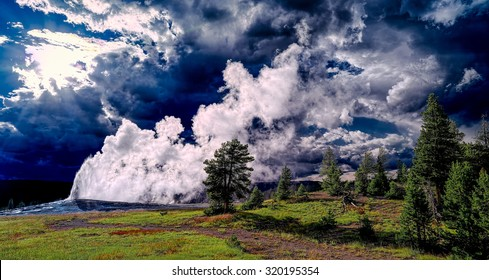 Old Faithful geyser and stormy cloud sunset. Panoramic landscape.  Wyoming, USA