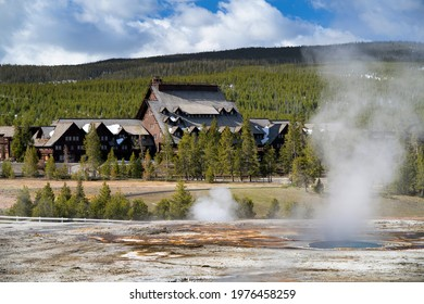 Old Faithful Inn with geysers and steam in foreground.