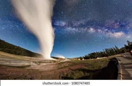 Old Faithful in Yellowstone National Park erupting under the Milky Way in Wyoming.