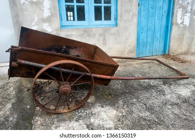 Old farm cart with two whells standing near house outdoor