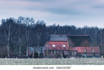 Old farm near winter forest under cloudy sky.