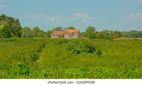 Old farm in a sunny green field with trees under a clear blue sky in Bourgoyennature reserve, Flanders, Belgium.