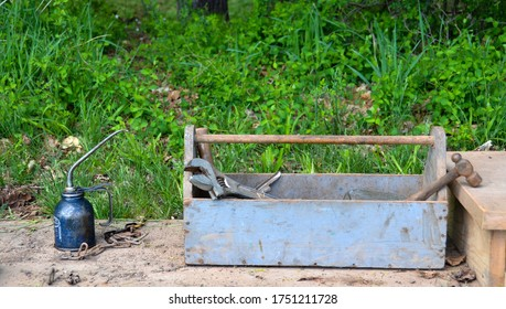 Old Farm tool box with tools and a oil can.