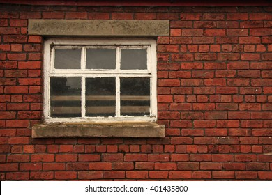 Old Farm window in red brick wall with stone lintel and cill