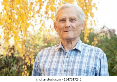Old farmer in autumn garden, close-up portrait. 80 year old European man looking at camera outdoors