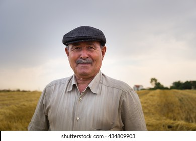 Old farmer is waiting in the middle of the field