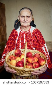 Old farmer woman in traditional costume holding a basket full of apples