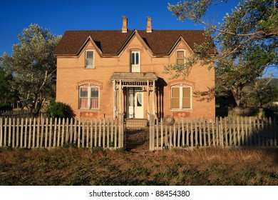 An old  farmhouse in a country setting, with a picket fence and trees around it.