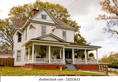 An old farmhouse with house plants on the front porch