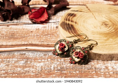 Old fashined earrings with potpourri on wooden table and wooden pad. Vintage jewelry with dark red roses, beauty. Golden earings with flowers.