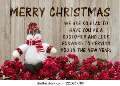 Old fashion Christmas greeting, Frost covered red holly berries with a snowman on weathered wood background with text Happy Holidays and appreciating business