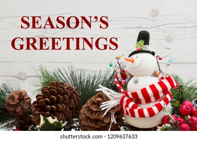 Old fashion Christmas greeting, Garland with a snowman, pine cones and red holly berries on weathered wood background with text Season's Greetings