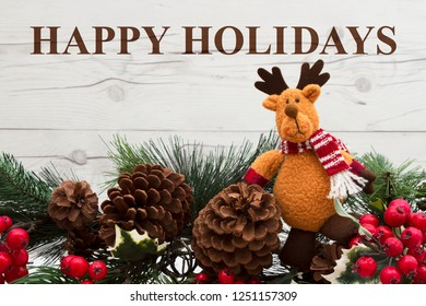 Old fashion Christmas greeting, Garland with a reindeer, pine cones and red holly berries on weathered wood background with text Happy Holidays
