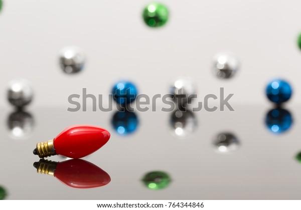 Old fashion Christmas light bulb on reflective surface