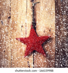 Old fashion christmas ornaments hanging on wooden background with white snowflakes. Rustic Christmas Decoration. Vintage Red Star.