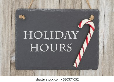 Old fashion Christmas store message, A retro chalkboard with a candy cane hanging on weathered wood background with text Holiday Hours