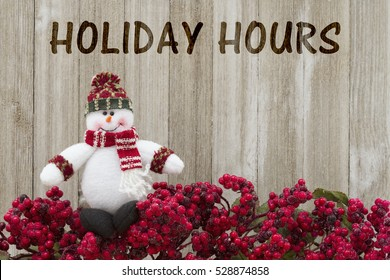Old fashion Christmas store message, Frost covered red holly berries with a snowman on weathered wood background with text Holiday Hours