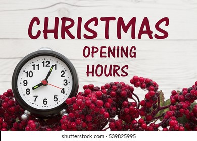 Old fashion Christmas store message, Frost covered red holly berries with an alarm clock on weathered wood background with text Christmas opening hours