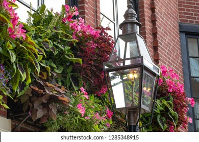 Old fashion gas street lamp in a glass lantern, with colorful flowers in a window box planter in the background, and space for text on the left