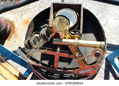 Old fashion sextant and compass on a stand on the harbour.