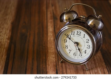 Old fashioned alarm clock on wood table  background
